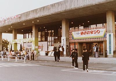 市民会館の入り口。右の緑色の立て看板には「春日井市民の歌発表会」と書かれています。